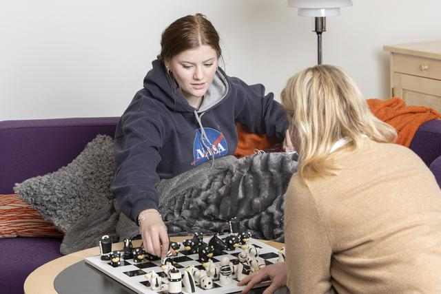 Teenage girl in a black hoodie and her mother playing a game.