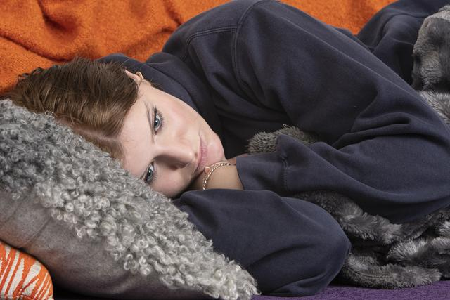 Teenage girl lying on a grey pillow in a sofa.