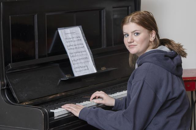 Teenage girl in a black hoodie playing piano.
